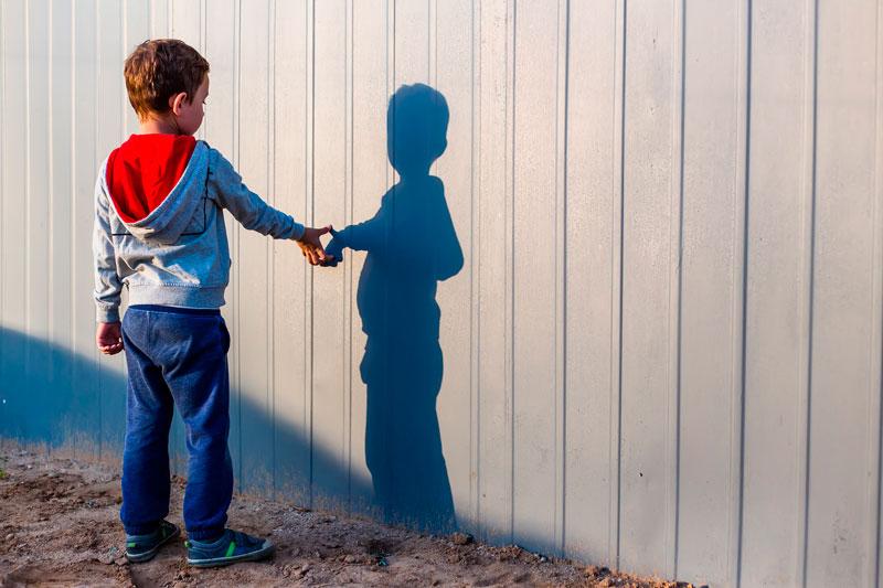 niño habla y juega con su sombra